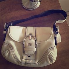 """coach shoulder bag. Ivory coach shoulder bag. Authentic! Has pinkish stain (see 4th pic) which is the only defect. I don't have leather cleaner so I'm not sure if it'll come off. Measures approx. 7""""x10"""". Strap measures approx. 10"""" and can be adjusted to make shorter. Priced accordingly. Coach Bags Shoulder Bags"""
