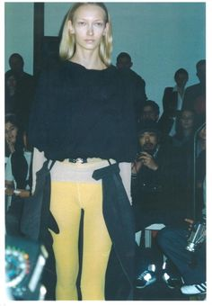 Lutz F/W 2000/2001 THE 1st SHOW , Paris. 'THE DEBUT' Images from the 1st Show, in Fabrice Hybert's Studio in Paris, February 2000: High Waists, Tights knitted with industrial Lycra worn with heavy draped Sweater and Overskirt, Pockets cut in the shape of gloves peak out from under a jacket.