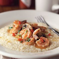 """A legendary morning repast in the Carolina Low Country, shrimp and grits is said to have begun as a fisherman's breakfast, created by shrimpers using the days catch. Original recipes called for sautéing the small local shrimp in butter and serving the seafood as a topping for creamy, stone-ground grits. Today, """"New Southern"""" variations abound, as creative cooks embellish the classic dish with everything from bacon and mushrooms to fresh truffles."""