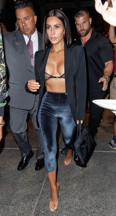 Kim Kardashian wears nothing but a sheer bra under a blazer paired with velvet pants and clear heels while out in NYC.