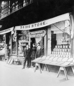 People stand outside in front of the doorway of a dime store,  posing for this photo.