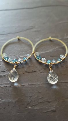 Beautiful blue colours make these earrings sparkle! Genuine blue topaz contrasts with neon blue apatite simply wrapped on gold filled hoops. Clear rock crystal briolettes are suspended from each, giving these earrings a finished chandelier style. - Materials: 14 kt gold filled earring hoops and components, blue topaz, blue apatite, rock crystal. - Measurements: 1.5 inches length or 4 centimetres, and 1 inch wide or 2.5 centimetres - This item is ready to ship! - Your earrings will be shi...