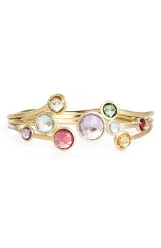 Marco Bicego Jaipur Triple Row Bangle   Colorful stones cap wavy threads of hand-engraved, 18-karat gold to form an open cuff with gorgeous sparkle.  Approx. width: 7/8 at widest point.  Actual stones may vary.  18k gold/tourmaline, quartz, peridot, rhodolite garnet, iolite, tanzanite, aquamarine, apatite, topaz, citrine, lemon citrine or amethyst.  By Marco Bicego; made in Italy.
