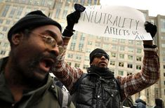 """A black man wearing a black vest holds up a sign that says """"Net neutrality affects us all."""""""