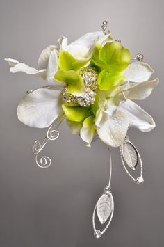 This corsage design features silk Orchids & Hydrangea Petals along with the Spectacular Design Leaves and Blingella Beads from Fitz Design. All available at: www.pioneerwholesaleco.com. Design by Tom Bowling, AIFD, PFCI.
