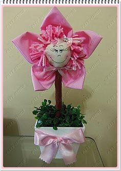 Vaso feito com flor de tecido, bonequinha feita também em tecido, cabelo de lá, vaso de MDF , grama artificial e fita de cetim. As cores do tecido e laços podem ser variados. R$ 13,00