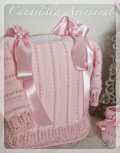 """Sideways stockinette and garter in (acrylic/wool?) pale pink baby weight yarn combined with eyelet rows in darker rose perle cotton (""""Jour Horizontal Anglais""""). Crab stitch or reverse crochet on neck; lace edging on hem and cuffs"""
