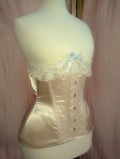 Nude satin under bust corset with vintage lace in cream and pale blue satin ribbon. By Corsets by Nasty Ginny.