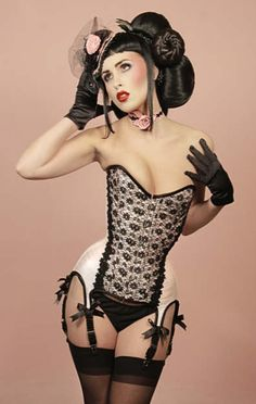 Pale Pink overbust corset in silk with black lace overlay and floral applique. Attached 6 shirred garters with satin bow