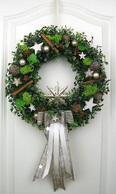 Weihnachtskranz mit einer dekorativen Schleife verziert mit Kunst- und Naturprodukten wie Weihnachtskugeln in creme, gold Tönen, weißen Sternen, Zimtstangen, Sternanis, Zapfen, künstlicher Tanne, Buchs, Efeu und Moos auf einem Strohkranz