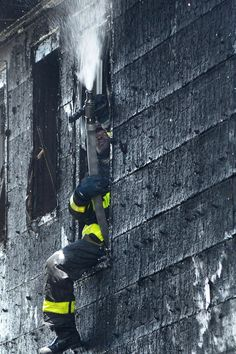 An FDNY firefighter helps knock down a two-alarm fire that burned through two homes in Hollis, Queens on June 26, 2014. The fire, that occurred on Hiawatha Avenue, reportedly injured 3 people but completely damaged both homes.