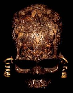 DAYAK CARVED: HEAD HUNTING HUMAN TROPHY #9  SKULL WITH TWO BRASS EARRINGS + RATTAN LASHING  HAND CARVED HUMAN BONE  THE DAYAK TRIBE, FROM BORNEO ISLAND  INDONESIA, CARVE DESIGNS INTO THE SKULLS  OF THEIR HEADHUNTED VICTIMS AND INSERT WOODEN FIGURES.