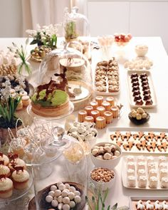 """Keep the food spread visually appealing. """"I like to group like with like, displaying bites in an organized, pleasing way,"""" says Darcy.Candy, nuts.com, sugarfina.com, jellybelly.com. Cupcakes, $2.75 each, onegirlcookies.com. Winter deer cupcake toppers, $4 for 12, shopsweetlulu.com. Chocolate deer (under cloche), andiespecialtysweets.etsy.com. Flowers, seaportflowers.com. Mini birds' nests, $12 for 12, beau-coup.com. Birch rounds, from $1 each, michaels.com."""