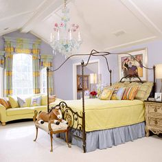Canopy beds offer elegant flair to any bedroom. Hanging artwork is another way to give a kid's room grown-up appeal. The playful chandelier adds a bit of whimsy to the room, an element crucial to any kid-friendly space. Piles of accent pillows on the bed and sofa add color and comfort