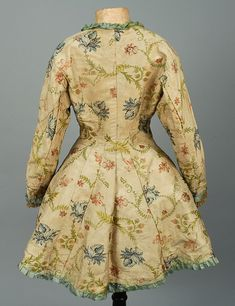 Rear view, jacket, America or Europe, 18th century. Off-white silk brocaded with tone on tone scrolling foliage and polychrome floral having square neckline, three quarter sleeve and full skirt with slight cutaway front, trimmed in pleated blue satin, sleeves edged in ecru lace ruffles, hook & eye closures, cotton lining.