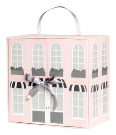 Light pink. Small dollhouse in cardboard with a printed motif. Doors with concealed magnetic fastener, tie at front, shelf inside, and handle at top. Size