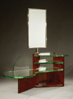 René Joubert (1878-1931) and Philippe PETIT (1900-1945) . An exceptional unusual dressing table in burr walnut with modernistic several thick glass shelves and a pivoting mirror.  Circa 1930.