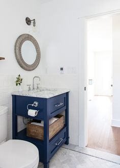 Navy bathroom vanity, herringbone Carrara marble floors, wine crate to hold towels