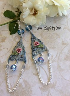 Chandelier Earrings .. Earring connectors dangle under a beautiful crystal glass bead, A rose and leaf and attached to the center of the connector with glass beads, crystals, silver chain dangling at the bottom .. FOR SALE .. $26.00 https://www.etsy.com/shop/CleverDesignsbyJann