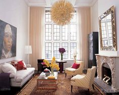 A crystal chandelier and 1940s églomisé mirror add drama to this soaring living room.