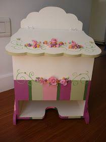 El set consta de una pañalera de madera pintada con aplicaciones en porcelana fría y una caja portacosméticos haciendo juego.