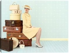Young woman wearing vintage travel clothes, sitting by vintage luggage print by Laurence Dutton at Photos.com 200350118-001 - If you have a friend who loves to get dressed to the nines for travel, this is the print for her!