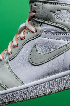 """Jordan Brand put the perfect finishing touch on its Summer 2021 release cycle with the Women's Air Jordan 1 High """"Seafoam,"""" a clean look for Michael Jordan's first signature shoe that features laces with unique orange trimming."""