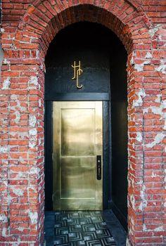 a recessed brass door behind an arch of brick