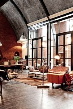 Beautiful loft space with soaring windows and a curved concrete ceiling. The dark wood floor and black window frames work with the concrete to give this space a modern.