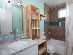 This room's grimy surfaces looked ready to condemn, but Curtis and Amanda were able to reface the original tub and toilet to save renovation dollars. Intricate custom tile work in the shower adds beachy style, while the wooden shelf gives the bathroom a rustic feel.
