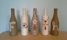 Upcycled bottles FAITH wrapped in jute, rope, and yarn with lace and button accents. Home decoration in neutral rustic color scheme.