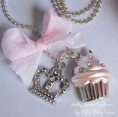 """My Cupcake Princess Necklace features a lead free, rhodium plated 15 x 20mm pink frosted cupcake with sparkly Czech crystals, a 15mm lead free, alloy and rhinestone crown and a sweet, hand-dyed pink ribbon bow. The necklace chain is a sophisticated, nickel-free, teeny tiny ball chain with a 15"""" or 16"""" drop. My Cupcake Princess Necklace contains small parts that can pose a choking hazard. They should not be worn by those under 4 years old!"""