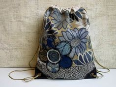 UPCYCLED~~REPURPOSED~~DRAWSTRING CINCH SACK BACK PACK in an easy color palette of neutrals and blues. A floral motif woven fabric covers the