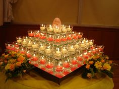 Various sizes of square mirrors (use small candleholders - dollar store - to separate tiers) wih tealights in clear glass containers