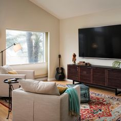 A large window, indented slightly from the living room walls, lets in a rush of natural light controlled by the accordion blinds. A big screen television is mounted above an Asian style cabinet creating an entertainment center area with concealed storage. A multicolor rug beneath a pair of neutral, contemporary chairs livens up the space.