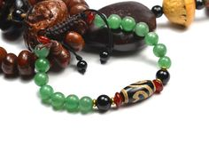 Elegant Tibetan Lotus Dzi Eye Jade Bracelet by FortuneJadeJewelry, £32.00 Made by Tibetan Dzi bead size: 2.0 cm x 1cm x 1 cm 8 mm green jade beads  4 Red Agate decorative beads 14 - 0,8 cm  2 Black Agate Beads Adjustable Bracelet 7 -10 inches   Free for all customers Perfectly wrapped jewelry gift box with ribbon, thank you letter within handmade oriental envelope envelope.