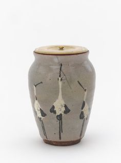 Kenzan-style powdered tea container with designs of standing cranes  late 19th century    Ogata Kenzan , (Japanese, 1663-1743)   Meiji era     Buff clay; white slip, iron pigment under transparent glaze, ivory lid.  H: 8.2 W: 6.0 D: 6.0 cm   Kyoto, Japan