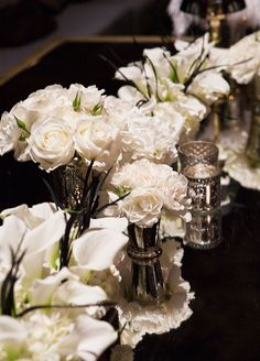 Beautiful white flowers are placed on top of the mirrored table runner. #weddingcenterpiece