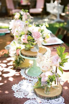 pink and mint wedding reception decor at outdoor table with cake stand and wood cut centerpiece platforms