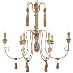 Adorned with antique gold tassels and bell shapes, this romantic and regal chandelier will be the focal point of the room. Six swirling metal arms hold candelabra lights among the gilded details of this delicate fixture. A gold adjustable chain allows the piece to be placed at the perfect height.
