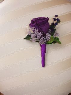 All the groomsmen have white roses with purple flowers and Kevin has purple with white possibly. Or vice versa.