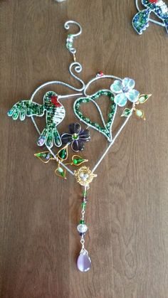 Wire wrapped beaded sun catcher with flowers and hummingbird and nest and ladybugs.