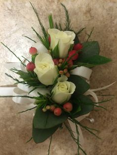 white spray rose corsage with peach hypericum berries and accent greens
