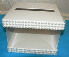 OFF WHITE WEDDING ADVICE, CARD HOLDER   THIS OFF WHITE CARDBOARD AND PLASTIC CARD HOLDER IS DECORATED WITH FAUX PEARL MESH RIBBON. THESE ARE NOT REAL PEARLS . THIS BOX CAN BE USED AS A CARD HOLDER FOR A WEDDING RECEPTION OR AN ADVICE BOX FOR A SHOWER. THE CARD HOLDER MEASURES 5 3/4 HIGH AND IS 7 3/4 X 7 3/4.   Thanks for looking