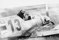 A soldier peers into the cockpit of a downed Messerschmitt Bf 109E. This is probably Bf 109E-1 (W.Nr. 3576) 'Red 13' of 7./JG 54, flown by Uffz. Zimmermann, which crashed near Lydd in Kent on 27 October 1940.