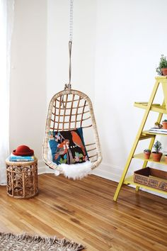 Hanging wicker chair in the corner by wood stove.