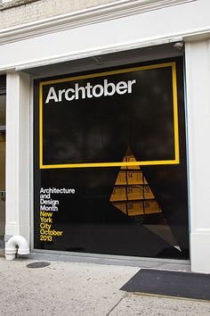 The storefront window of the Center for Architecture has been blacked out except for a triangle cutout.