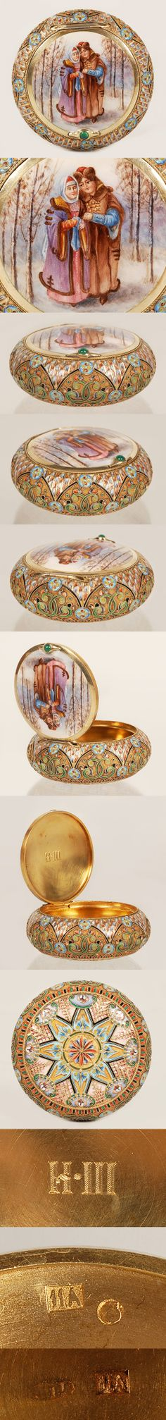 A Russian silver gilt, cloisonne and enplein enamel snuff box, 11th Artel, Moscow,circa 1908-1917. Of circular form, the hinged lid painted en plein with a pictoral enamel scene of a Russian man and woman in costume sttanding in a grove of trees on snow covered ground. The sides and bottom are enameled with geometric and floral motifs