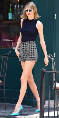Taylor Swift showed off her enviably long legs in NYC wearing a pair of high-waist graphic-print shorts that she styled with a navy sleeveless top, a glittery Mary Katrantzou purse, Swarovski shades, and aqua pumps.