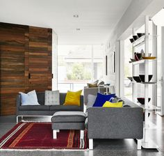 This small, contemporary living room is made complete but the grey modern couch with stainless steel footers. The couches match excellently with the built in shelving and surprisingly this cherry wood wall décor!